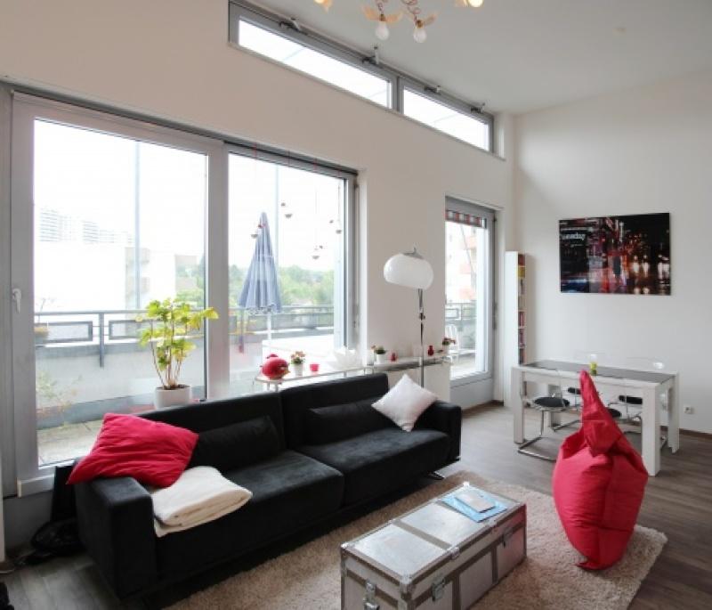 Das Wohnzimmer mit Zugang zum Balkon und Essbereich